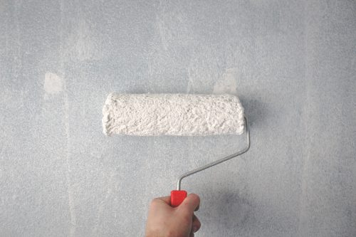 Roller with white paint painting grey wall