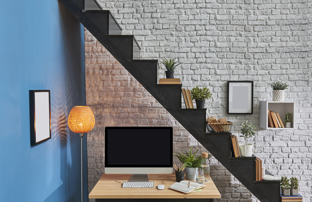 Black stairs in the room and working desktop wooden desk under stairs